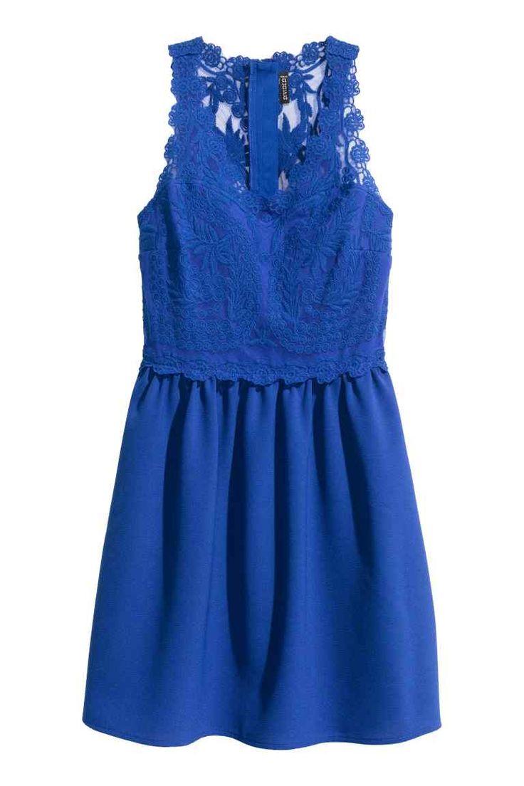 Čipkové šaty: Krátke šaty bez rukávov sčipkovým živôtikom so zapínaním na skrytý zips na chrbte asmierne rozšírenou sukňou zkrepovej tkaniny. Podšité.