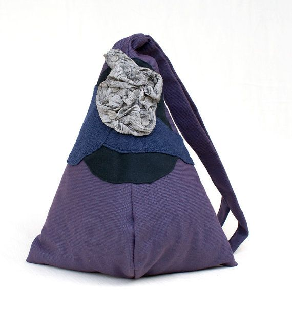 Backpack handmade with purple furniture fabric, decorated with gray iridescent crisp fabric and black/blue cotton. Secure zip closure on the back. Inside lining of white cotton, an interior zippered pocket, an interior opened pocket for cell phone. Always inside, a pochette with zipper, attached to the backpack with a drawstring.