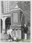 Tom Staassen en L.J.W. Hazelzet bij de pomp op de Markt.  Dateringca.1978.