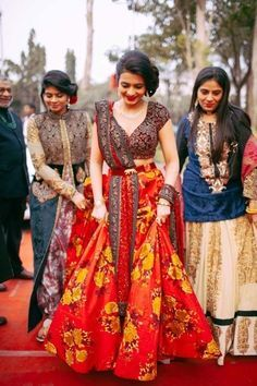 Sister of the Bride - Bride in a Floral Lehenga with a Marsala Blouse | WedMeGood | Floral Lehnga with a Belted Blouse and Dupatta and the Sister of the Bride in a Cream Lehenga with Blue Long Kurta, Long Cape with Pants #wedmegood #indianbride #indianwedding #sisterofthebride #sisterofthebrideoutfit #floral #lehenga #marsala #belt