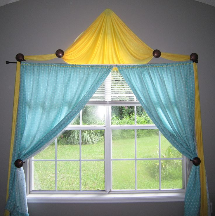 yellow and teal bedroom window treatment using curtain medallions (curtain holdbacks)
