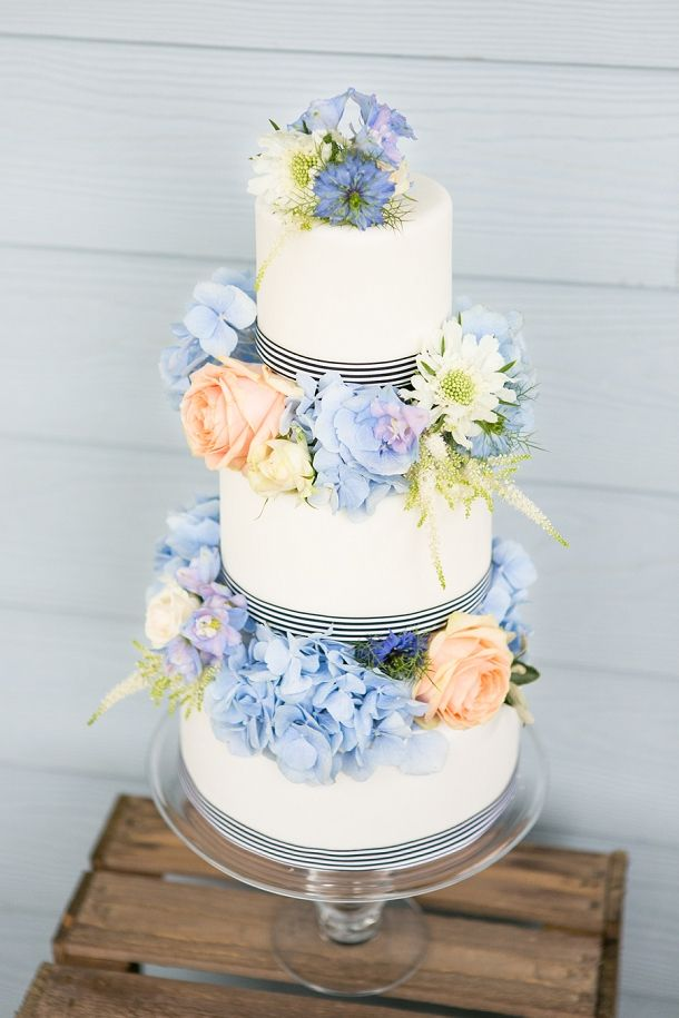classic wedding cake with peach & blue floral tiers and ribbon for a nautical wedding