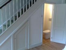 Toilet underneath stairs