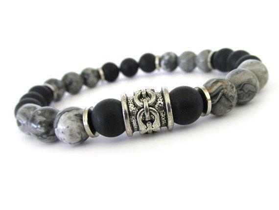 Gris bracelet masculin jasper avec perles onyx noir mat et accents en étain. Les perles de jasper sont 8mm avec des motifs complexes et de belles variations de gris et noir, complétés par les pierres Mats ce qui en fait un bracelet cool, hip pour nimporte quel mec. Portez ce morceau de bijoux pour hommes seul ou empilée avec dautres bracelets Rock & matériel, peut-être même ajouter dans une montre tendance pour un look élégant.  Bracelet mesure 8 et est réalisé avec cordon pour bijoux str...