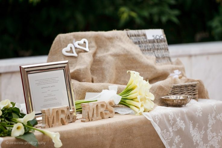 Welcome wedding table with burlap, white lace, calla lillies wedding bouquet and pic nic basket full of rice for the newlyweds!