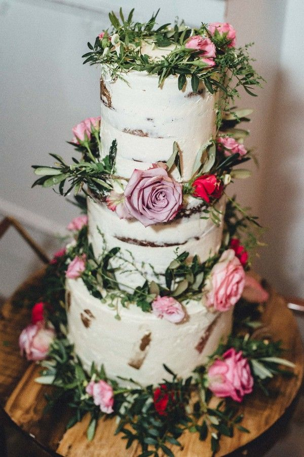 Gorgeous naked cake topped with green & pink floral decor | Image by Kreativ Wedding
