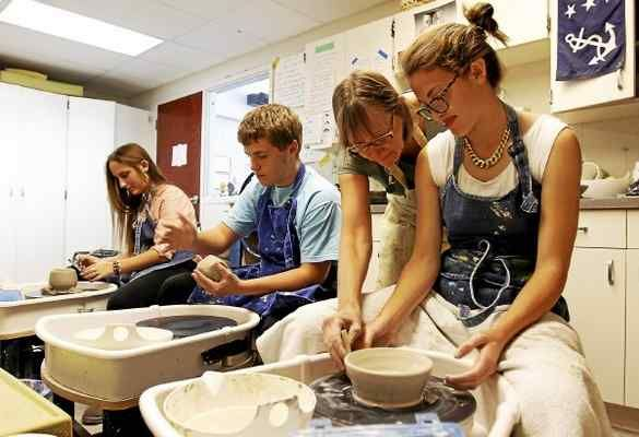 Sam Greene/The Morning Journal  Art teacher Ann Bort assists her student Claire O'Neill with a bowl at Lake Ridge Academy in North Ridgeville, Ohio, on Thursday, Oct. 10, 2013. The Lake Ridge art students hand spun multiple bowls each to be sold in the annual Empty Bowls charity even at Blesser Park in Avon Lake Saturday.