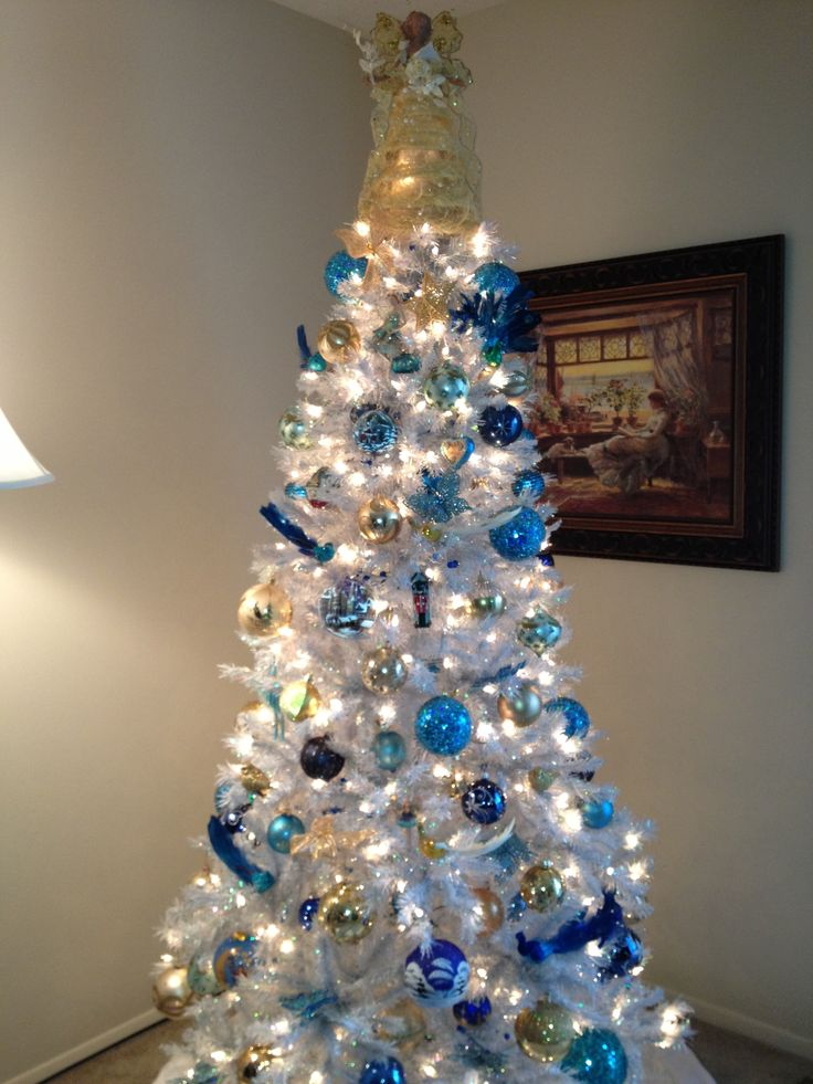 Blue and gold ornaments on a white christmas tree white christmas