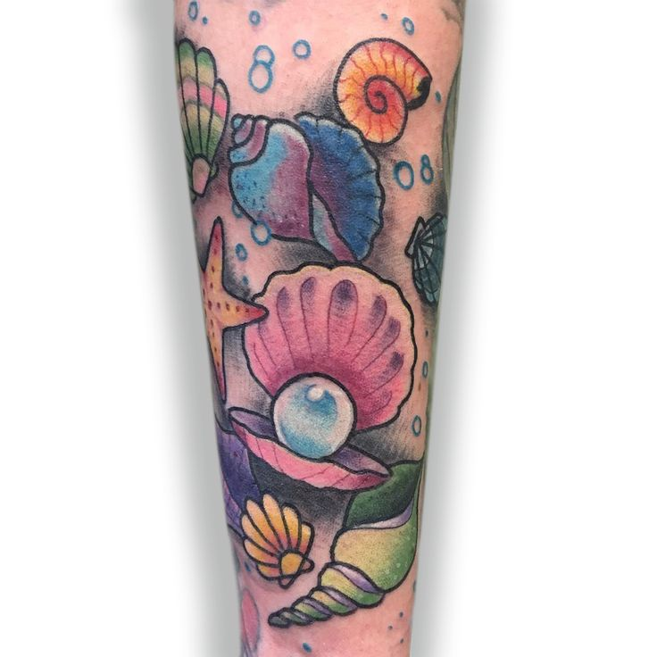 A color tattoo half sleeve, under the sea, of pearls and shells, done by @NiceJesTattoos.