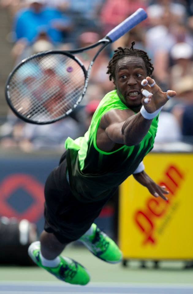 Gael Monfils tosses his racquet at the ball, hitting the ball and sending it over the net. Rogers Cup 3rd round play between Novak Djokovic (SRB) and Gael Monfils (FRA) on August 6, 2014, at Rexall Centre. Djokovic won 6-2, 6-7, 7-6 via Rick Madonik.