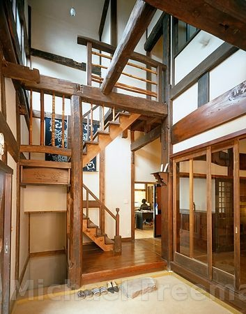 A modern Japanese home in Tokyo city designed in the style of a minka, a post-and-beam construction of traditional farmhouses that makes them capable of being dismantled and re-assembled despite their size. The entrance displays a complex structural pattern of pillars and cross beams, rising the full two-storey height. In order to withstand earthquakes. photo by Michael Freeman.