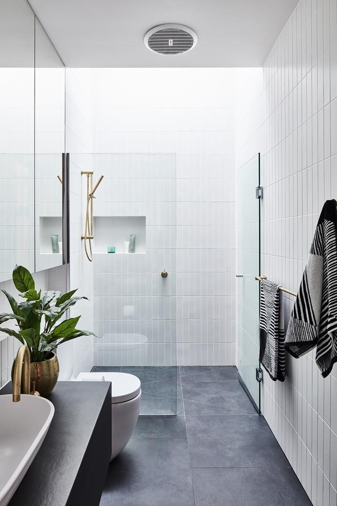 The bathroom and laundry both feature 600mm porcelain floor tiles in Charcoal and 60mm x 240mm ceramic wall tiles in Matte White. Tapware and hardware from Sussex Taps.
