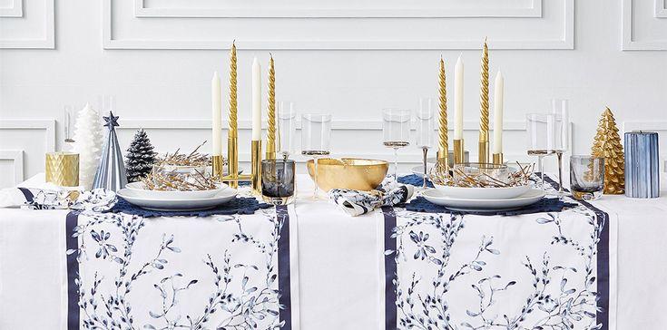 Esta mesa navideña es elegante gracias a los caminos estampados con flores azul y blanco y las velas y otros detalles en dorado.