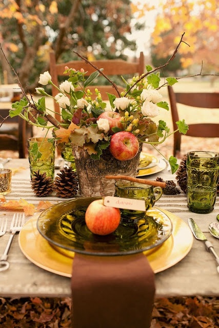 Beautiful tablescape for a fall party.  Looks like a small stump carved out to hold flowers.  Flower arrangement includes apples