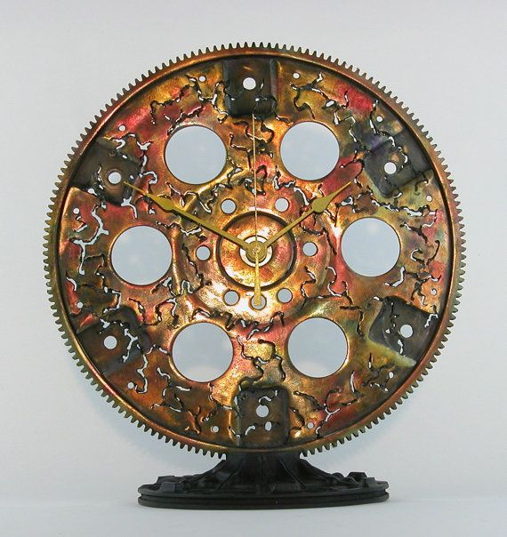 Handmade clocks by sculptor William Wilmot. Welded steel. Salvaged auto, truck, car, bicycle, aircraft parts. Industrial. Steampunk. Retro-futuristic. Atomic Ranch.  Custom clocks may be ordered in sizes and colors to suit your decor. Unique gifts for motor sports enthusiasts, gear heads, petrol heads, car collectors, industrial design, steampunk design, retro-futuristic design, Atomic Ranch design.  Desk clocks are $95 to $185. Table clocks are $105 to $385. Wall clocks are $285 to $485…