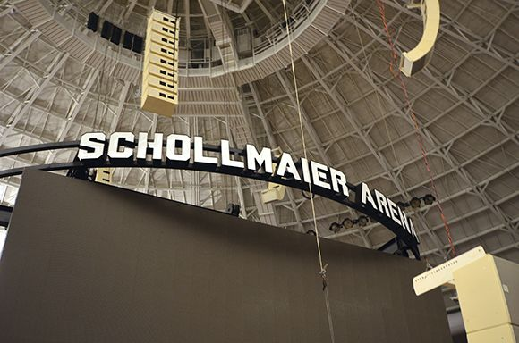 The video board under construction. The line arrays that were stored during construction are being placed in position (left), and the Schollmaier Arena sign on the top of the court video board is shown close to its final destination.