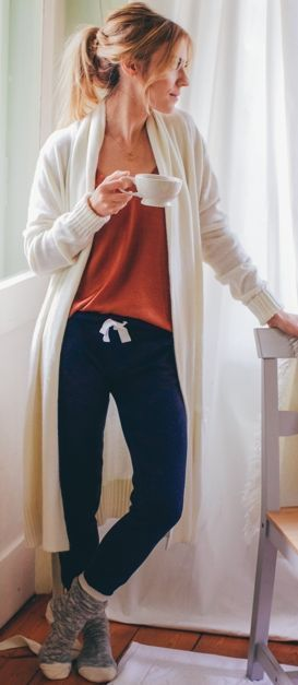 navy pants, an orange top, socks and a long white cardigan