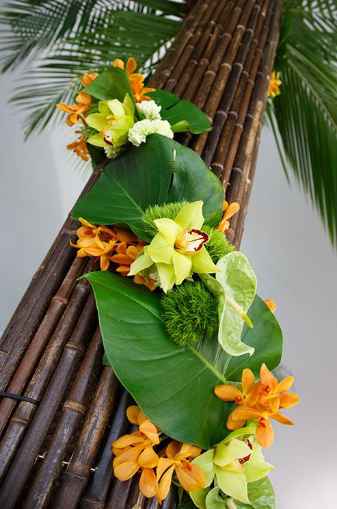 This tropical floral arrangement features a combination of orchids, leaves and…