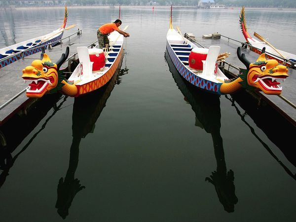 Dragon Boats Photograph by Guang Niu/Getty Images A man prepares a dragon boat for the Duanwu Festival races, held each year to honor the ancient poet Qu ...