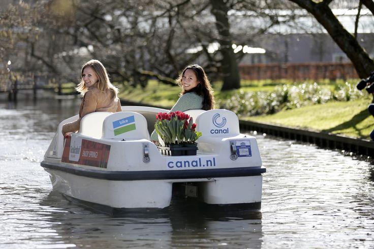 De waterfiets van Canal Company ligt aangemeerd bij de steiger van Bakker's Amsterdamse Tuin. Neem plaats en maak een leuke selfie met de beroemde Keukenhof-molen op de achtergrond!