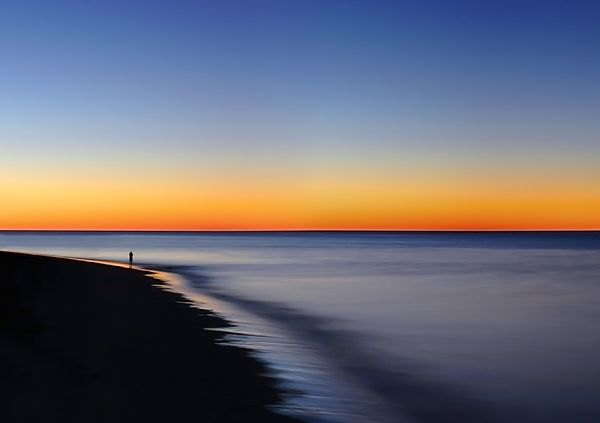A lone silhouette on the beach against a spectacular Hervey Bay sunset in Queensland, Australia