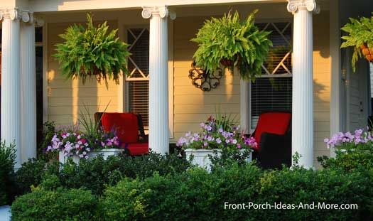 hanging baskets on porch--flowers underneath. Pretty colored chairs