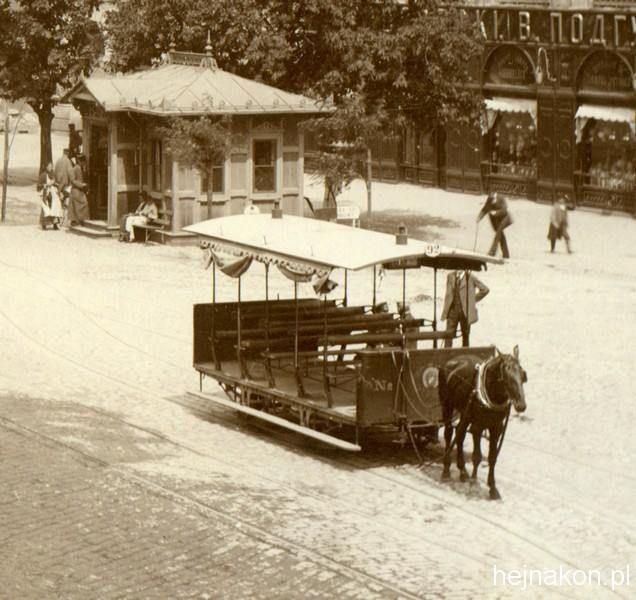 Ok. 1884 roku. Krakowskie Przedmieście. Wagon typu letni-spacerowy z płóciennymi zasłonami, został sprowadzony do Warszawy w 1882 roku. Na fotografii Konrada Brandla widoczna jest również stacja kryta dla pasażerów.