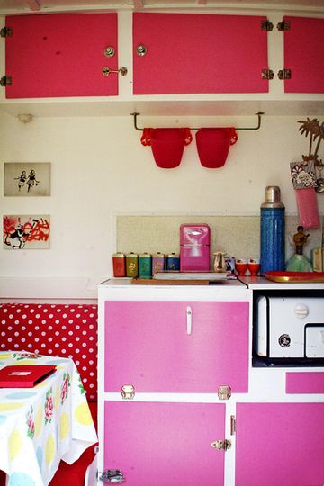 1964 Vintage Caravan Makeover --- Pink kitchen cabinets! And that vintage-looking yellow and blue dot with the pink flowers accent table cloth is to die for! (View #5)