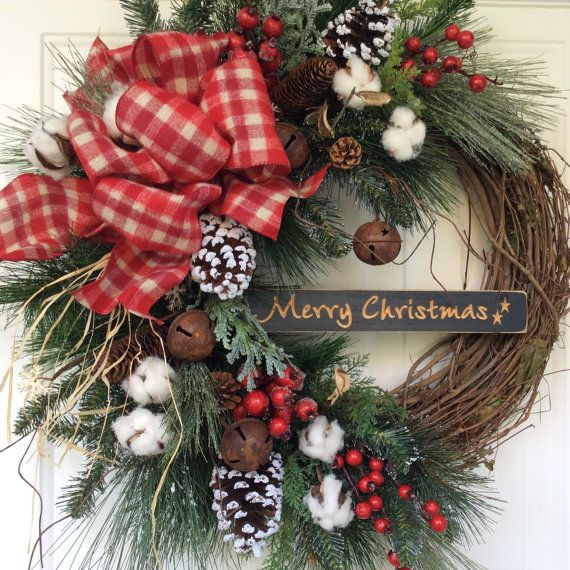 Christmas Wreath-Holiday Wreath-Winter Wreath-Jingle Bell Wreath-Wooden Christmas Sign-Christmas Decor-Cotton Boll Wreath-Wreath for Door Ring in the holiday season with a beautiful evergreen wreath on a grapevine base. This classic design is filled with realistic white pine, cedar, juniper, balsam and frosted scotch pine. Clusters of red berries and snow-covered natural pine cones adorn this farmhouse-style wreath and create a lovely foundation for an engraved wooden sign wishing all who…