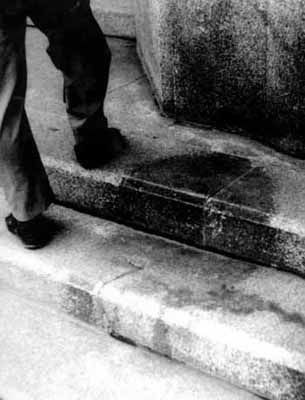 """Shadow of death: The stone steps at the entrance to the Hiroshima Branch of Sumitomo Bank, located 260 meters from the hypocenter, were imprinted with the shadow of an atomic bomb victim, the so-called """"shadow of death."""" This shadow was a consequence of the bomb's heat rays, a blistering 4000 degrees Celsius. In 1959, a fence was placed around this portion of the steps and, in 1967, the fading shadow was protected with reinforced glass."""