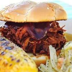 Texas-style pulled pork simmers in a tangy chili-seasoned barbecue sauce with plenty of onion, then pulled into tender shreds to serve on a buttered, toasted bun.