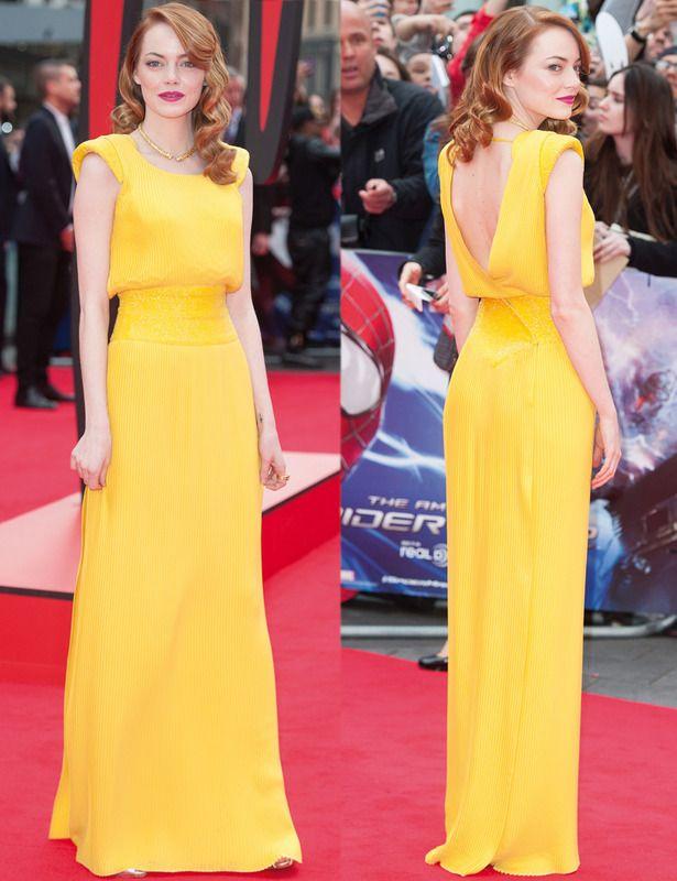 Emma Stone con un espectacular vestido amarillo plisado con detalle de Swarovksi en la cintura, hombros armados y espalda cruzada al aire de Atelier Versace.