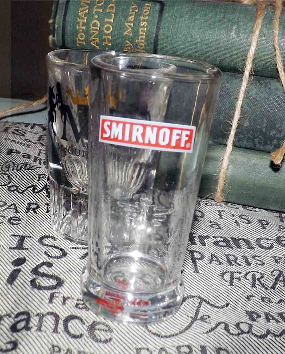 PAIR of vintage shot glasses.  One McGuinness Distilleries, one Smirnoff Vodka.  Commercial quality.