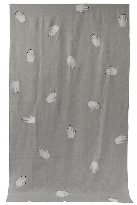 oatmeal throw patterned with white hand prints with black nails