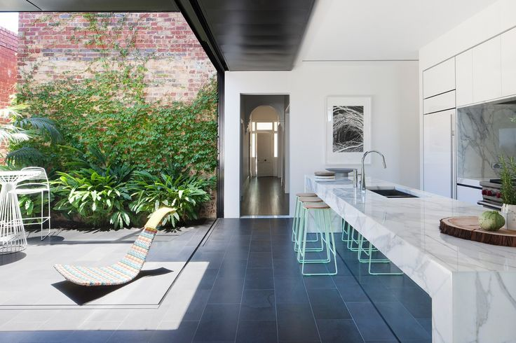 Indoor/outdoor kitchen: dark grey floor tiles, thick white marble benchtop with waterfall, marble splashback, white cabinets, tinted mirror on back of island bench, mint & wood bar stools
