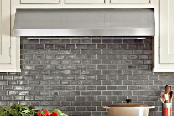 For a fresh take on classic subway tile, check out Ann Sacks' Stoneware Elements in New Mercury (about $35 per square foot). The metallic sheen on these mini rectangles picks up the shine of the stainless-steel appliances and chrome fixtures while softening the transition between black counters and white cabinets. | Photo: Eric Piasecki/Otto | thisoldhouse.com