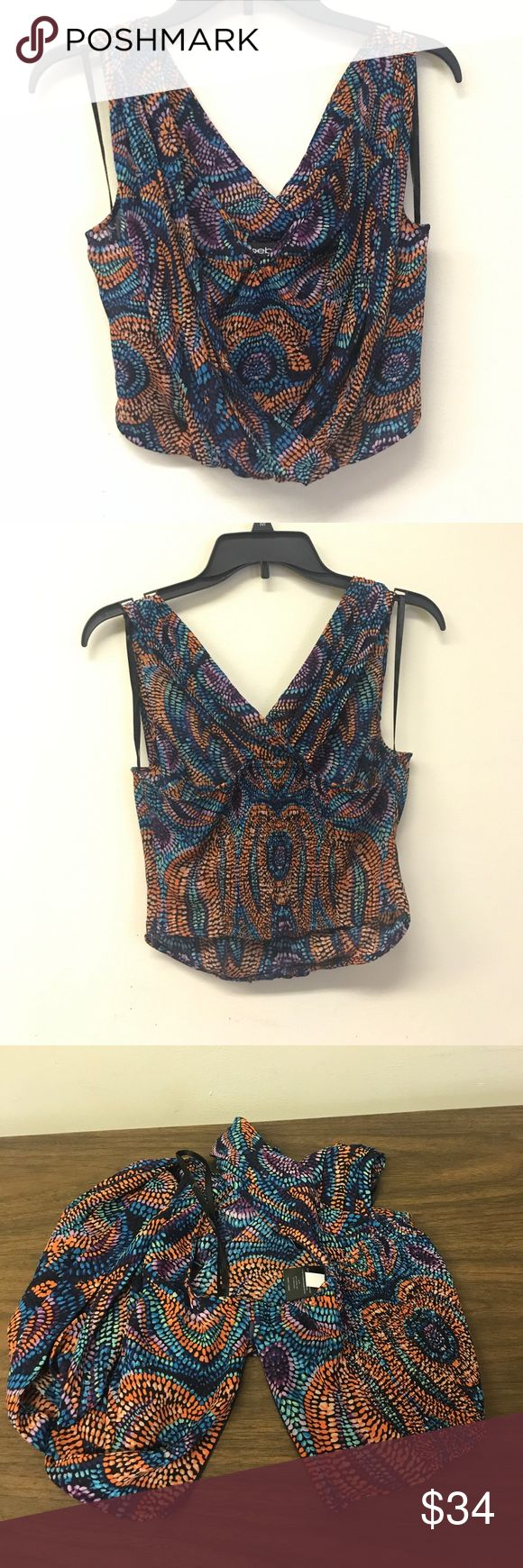 """NWT Bebe Blouse NWT! Bebe size XS Blouse. Multicolor pattern of orange, dark & light purple, mint, & dark & light blue dots over a very dark blue/black base. V neckline with 2 puckered & Draped pieces that cross over one another on front. Hidden zipper up left side hem for easy on/off. V back with a puckered elastic stretch panel down center back. Slightly cropped- looks great with high waisted pants. Length: 17"""". 100% Polyester. Price tag: $69.00 bebe Tops Blouses"""