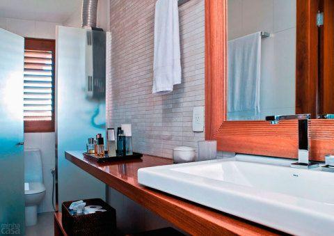 Um pranchão forma a bancada da pia deste banheiro projetado por Rosa Brandão e Mila Regina. Abaixo do tampo, módulos com rodízios guardam os itens de higiene. A parede do espelho recebeu acabamento de placas de porcelanato que imitam mosaico travertino.