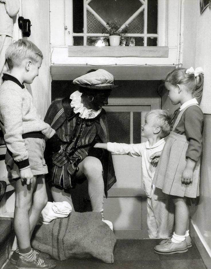 DUTCH 1950-60 Spaarnestad. Sinterklaasfeest, kinderen vol aandacht voor Zwarte Piet met juten zak.
