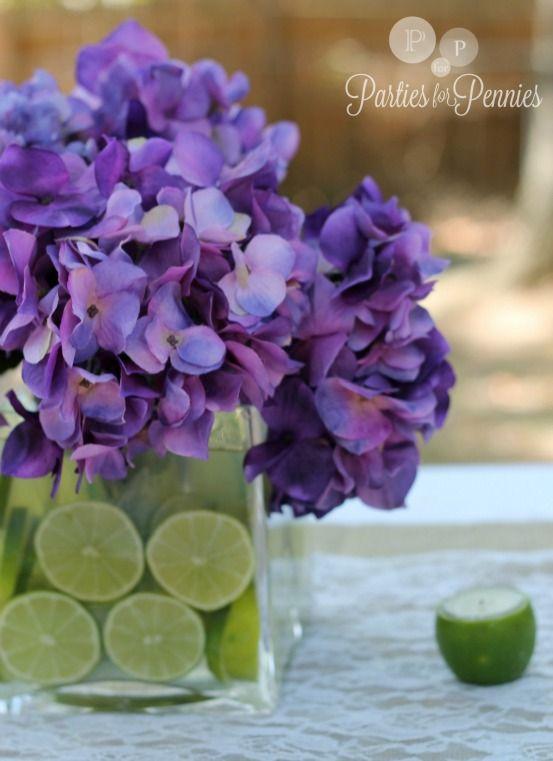 Centro de mesa con jarrón relleno de rodajas de limón y decorado con hortensias de color púrpura. #FiestaDiaDeLaMujer