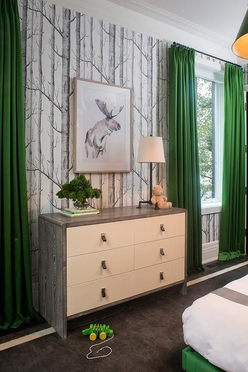 Gray and green boy's bedroom features walls clad in Cole & Sons Woods Wallpaper lined with a white and gray dresser, Bungalow 5 Niagara 6 Drawer, flanked by windows dressed in kelly green curtains.