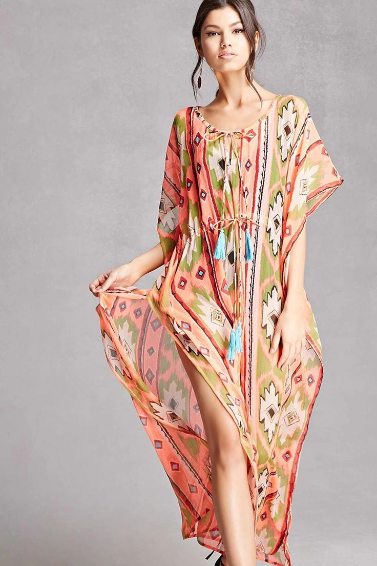 A sheer woven maxi dress by Z&L Europe™ featuring an allover tribal print, short dolman sleeves, a drawstring waist, a split neckline with tassels, and side slits.