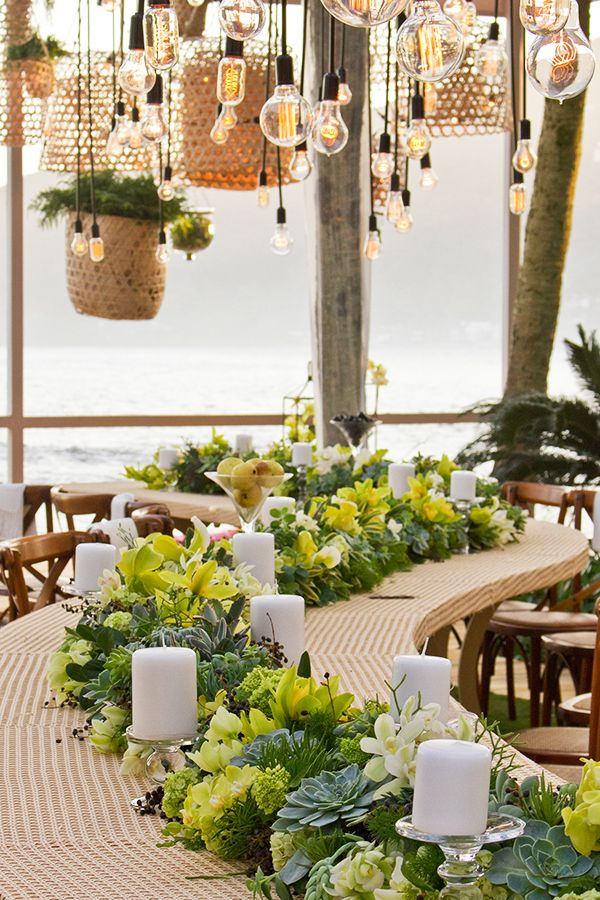 Casamento na praia com decoração moderna - mesa comunitária em formato de S - arranjos verdes com folhagens, flores e frutas - lâmpadas suspensas ( Decoração: Flor e Forma )