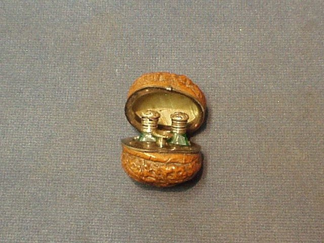 A lady's 19th Century carved walnut scent bottle holder, the interior with silver plated mounts revealing 2 miniature cut green glass perfume bottles with stoppers and a funnel