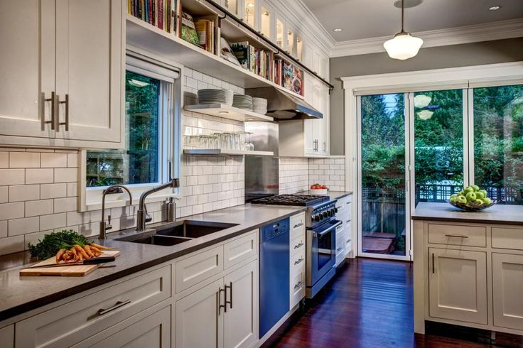 Open shelves keep cookbooks and everyday tableware nearby but off the countertops in this transitional kitchen. Roller shades on the glass doors and window allow for natural lighting or privacy. A white subway tile backsplash with gray grout complements the room's white and gray color scheme.