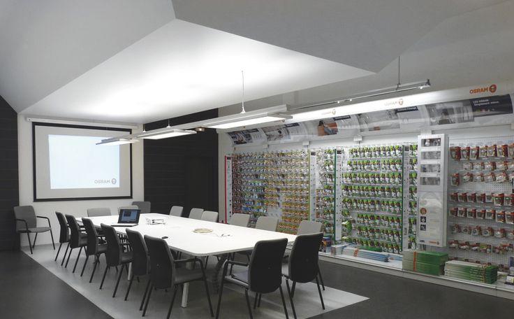 Au cœur de son siège social à Molsheim, Osram a aménagé une salle de démonstration, véritable vitrine de son savoir-faire. Au dessus de la table, un plafond en toile tendue a permis de réduire la grande hauteur du local et d'installer un rail avec 3 luminaires. #entreprise #plafond #lumineux #design #intérieur