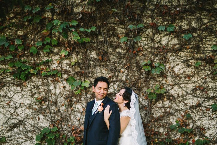 Los angeles fiesta themed wedding bride lace a line gown with illusion neckline and crystal belt with long lace veil and groom navy blue suit with matching vest and white dress shirt with long green plaid tie with orange floral boutonniere