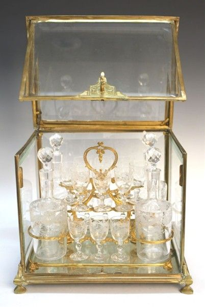 French Gilt Bronze, Brass & Glass Tantalus, Box tantalus with 4 Decanters and 16 liqueur glasses. The front and top unlock and open with a key and the interior cradle lifts out. Each decanter and glass has an etched pattern and the glass sides of the box are beveled. France, ca. 19th Century