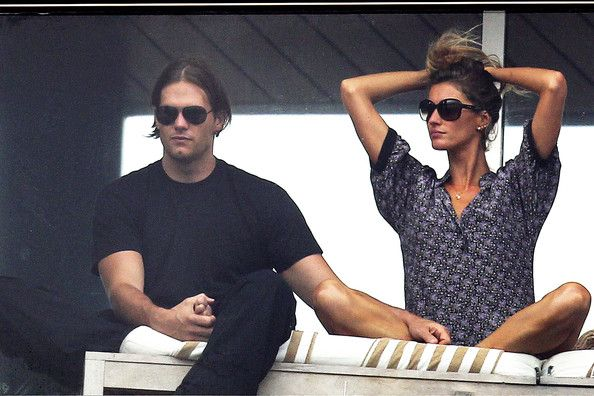 VIVA BRAZIL! Tom Brady and Gisele Bundchen enjoy each other's company while watching a street carnival with friends from their balcony in Brazil. Brady is seen removing the protective wrap from his right foot, but still wincing as he rubbed it. The football player, wearing a headband to keep his long hair out of his face, is seen drinking from a coconut and dancing with Gisele, who looked like she was enjoying herself with friends and family close by.