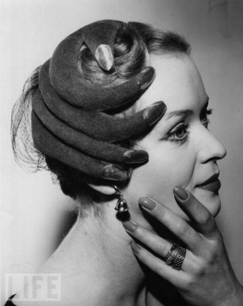 Model wearing a hat shaped like a hand for Life magazine, 1953